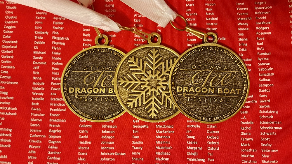 Picture of three of the participation medals from the event, with background being red souvenir jersey that has every participant's name on it.