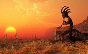 Image of the Kokopelli creature playing a flute, with orange sky and setting sun and desert in the background.
